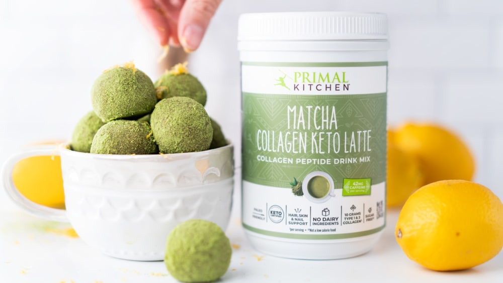 A hand sprinkling lemon zest on top of matcha balls stacked in a white bowl. Next to the bowl is a canister of Primal Kitchen Matcha Collagen Keto Latte Drink Mix and lemons.