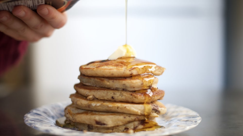Pouring maple syrup over chocolate chip pancakes