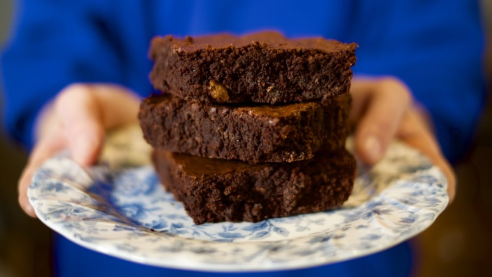 Brownies cut and stacked on top of one another, and ready to be eaten.