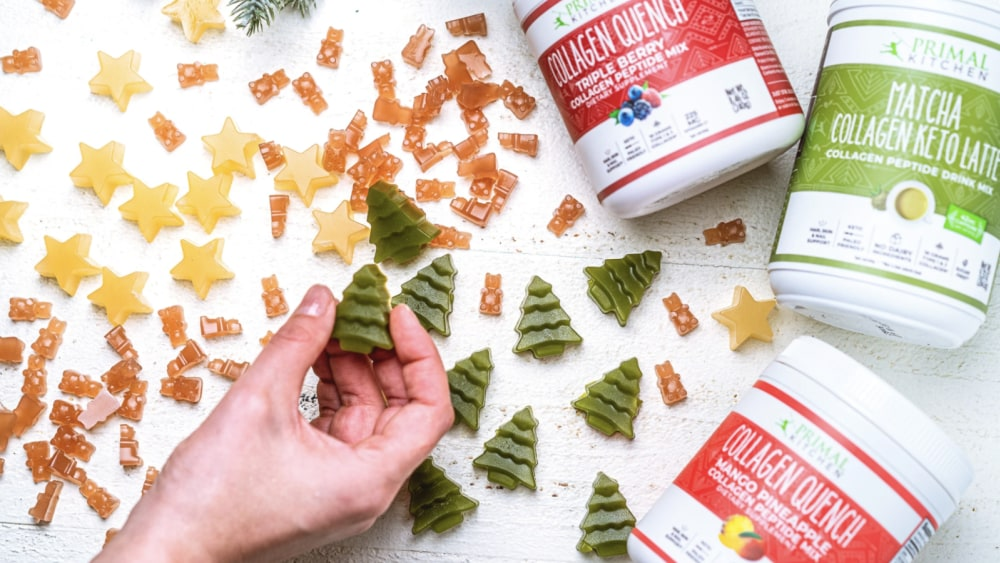 A hand holds a tree-shaped gummy, while collagen gummies, Collagen Quench® and holiday greens surround the hand on a white background.