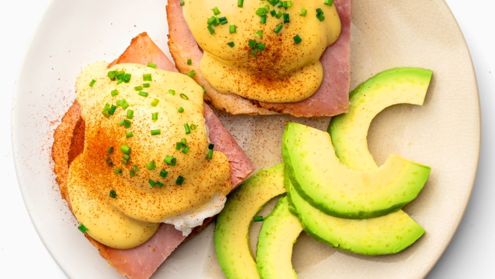 Close up shot of Keto eggs benedict: sliced ham with poached eggs, hollandaise sauce, chopped chives, and paprika on a white plate. Avocado slices are also on the plate.