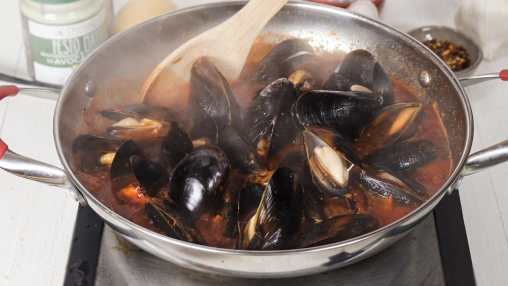 Mussels Fra Diavolo are stirred by a wooden spoon with pesto mayo and Arrabbiata Sauce in the background.