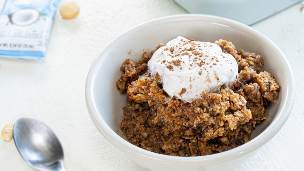 A white bowl filled with baked noatmeal topped with whipped coconut cream with a dusting of cocoa powder. A silver spoon and packet of Primal Kitchen Collagen Fuel - Vanilla is off to the side.