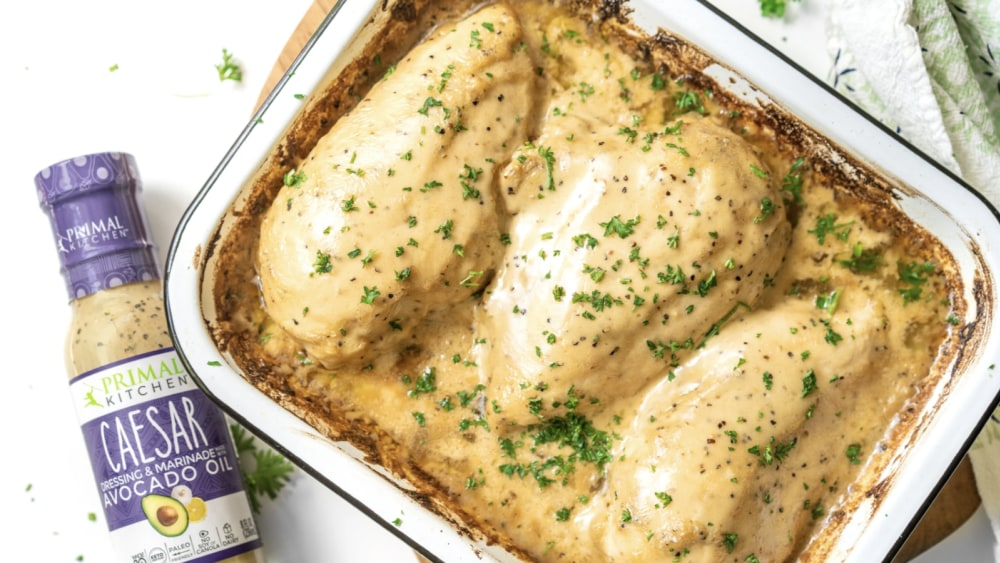 A bottle of Primal Kitchen Caesar Dressing is next to a white dish with Bake Caesar Chicken breasts.