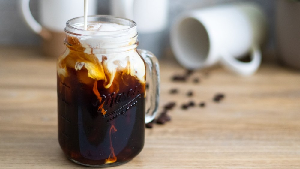pouring heavy cream over a dark extracted cold brew coffee over ice in a mason jar with the 12oz set of Mora Ceramics coffee mugs in the background