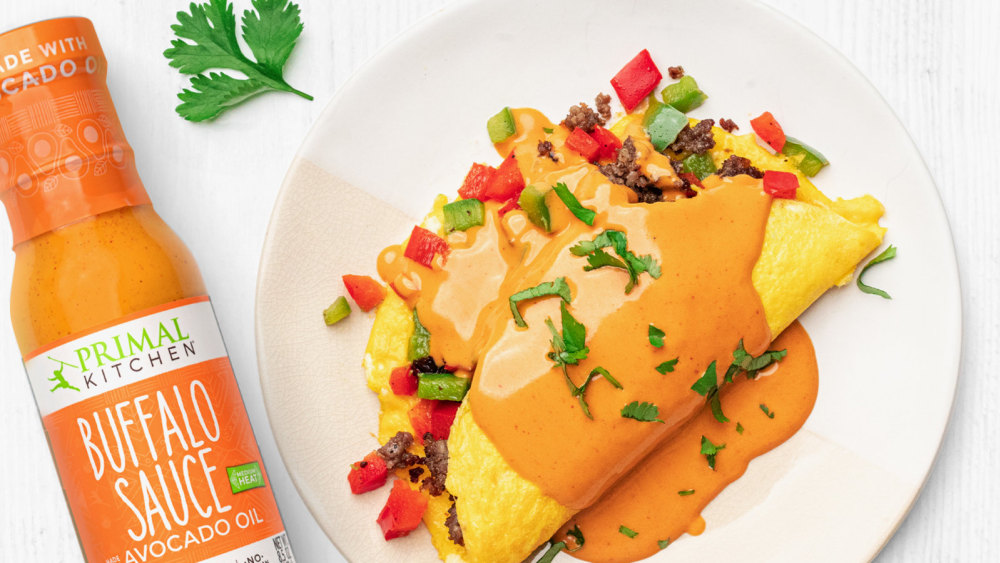 The southwest omelet is drizzled with Buffalo Sauce on a white plate, with buffalo sauce nearby.