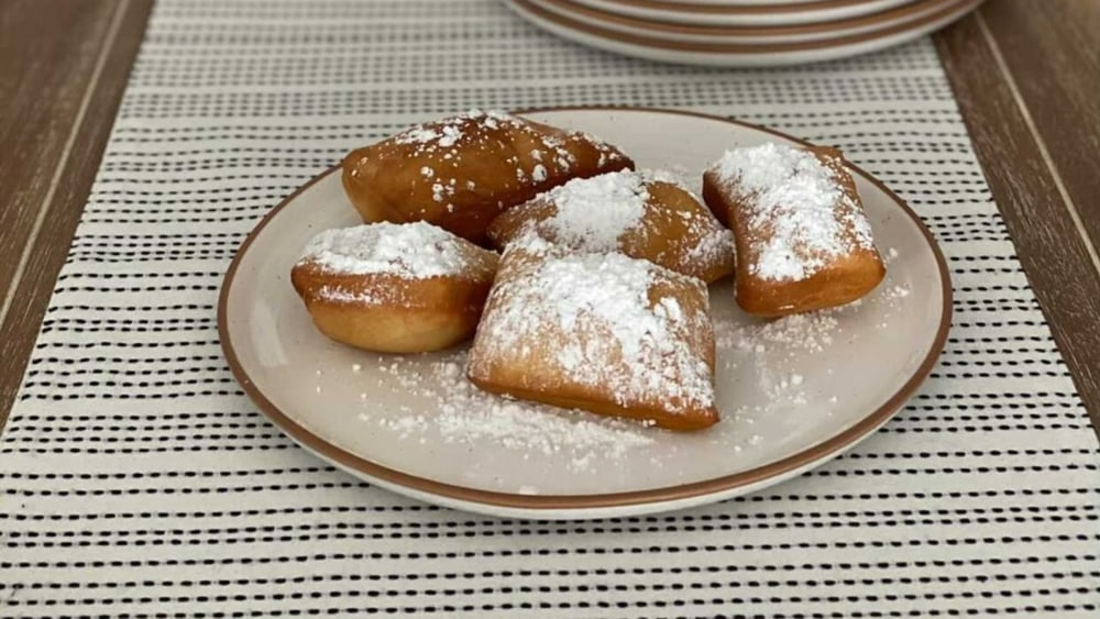 a plate of fried beignets with powdered sugar