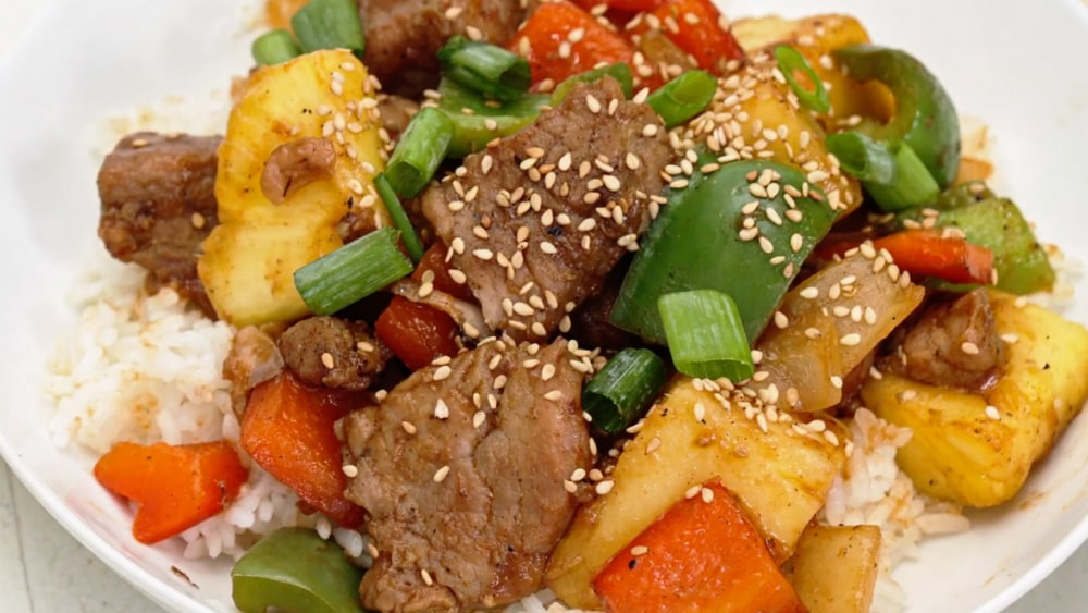A closeup of sweet and sour pork over rice.