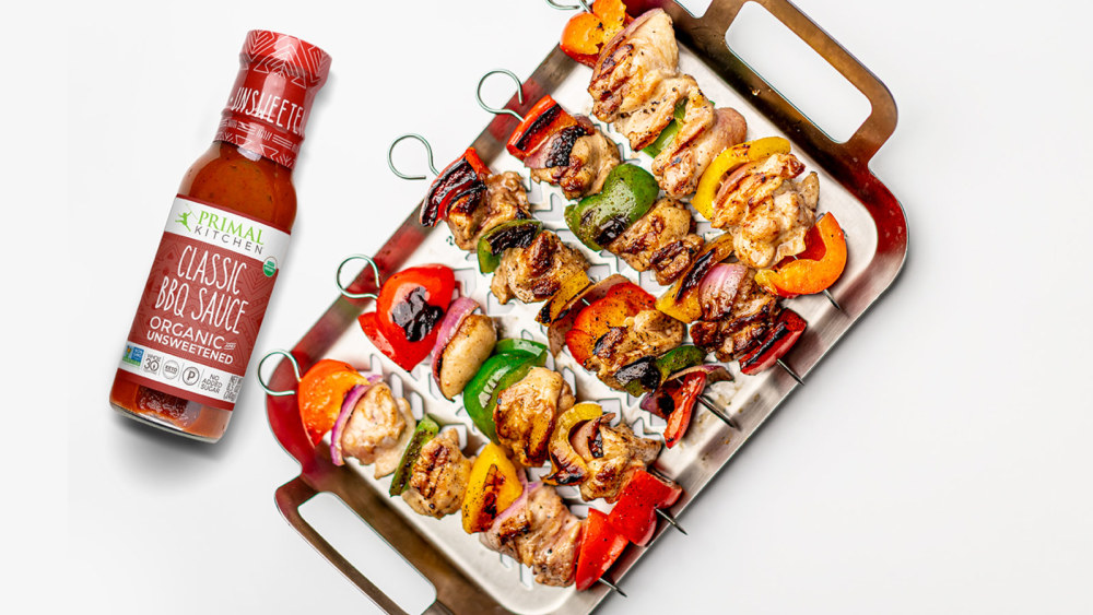 Grilled Chicken Kabobs with Vegetables are laid out on a metal pan with a bottle of BBQ Sauce nearby.