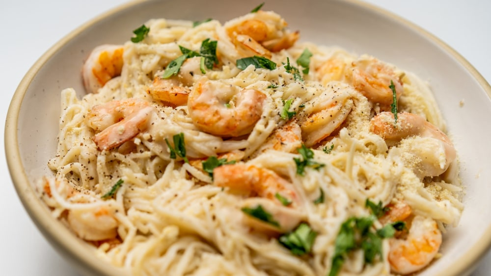 A cream colored bowl is filled with Shrimp Alfredo made with hearts of palm noodles.