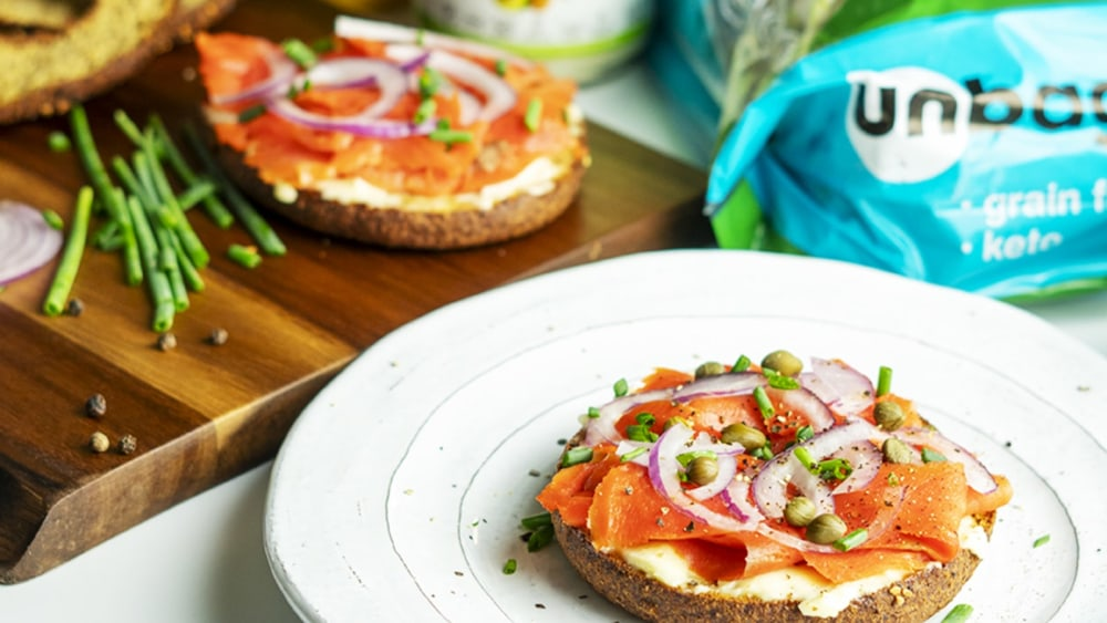 A white plate holds half of a smoked salmon breakfast bagel, with mayo, Unbun Bagels, and a cutting board with more ingredients in the background.