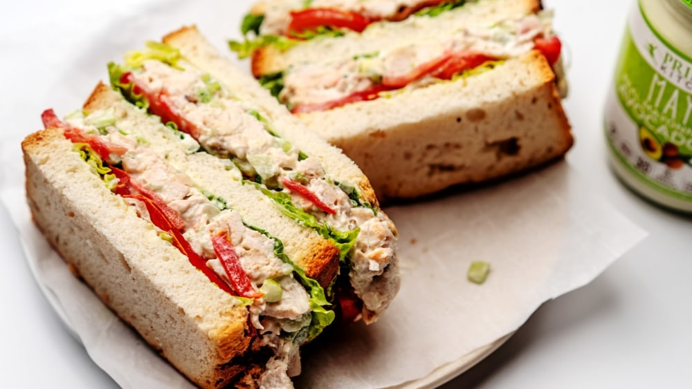 A white plate with two classic chicken salad sandwiches.