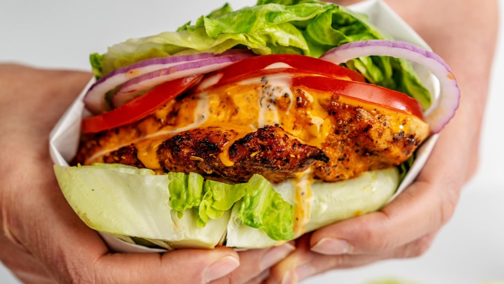 Two hands hold a grilled buffalo chicken lettuce wrap, dripping with buffalo sauce.