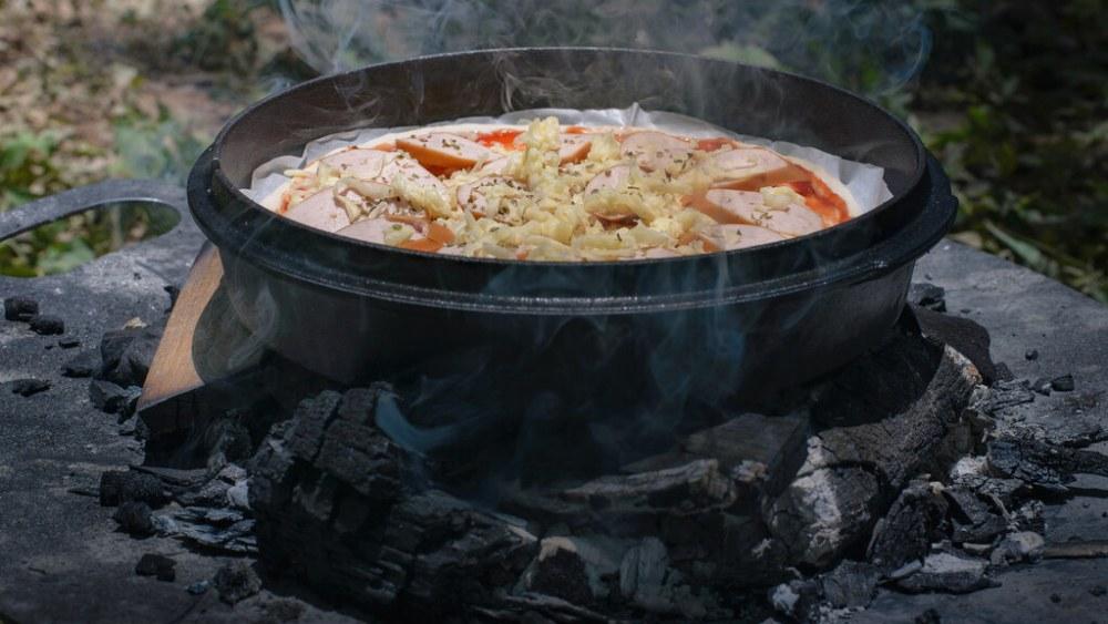 Image de Pizza au four hollandais: une recette fraîche de feu de camp