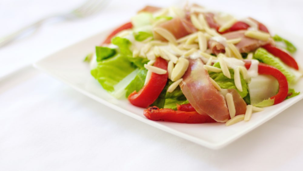 Image of Salad With Prosciutto Roasted Red Peppers And Creamy Almond Dressing