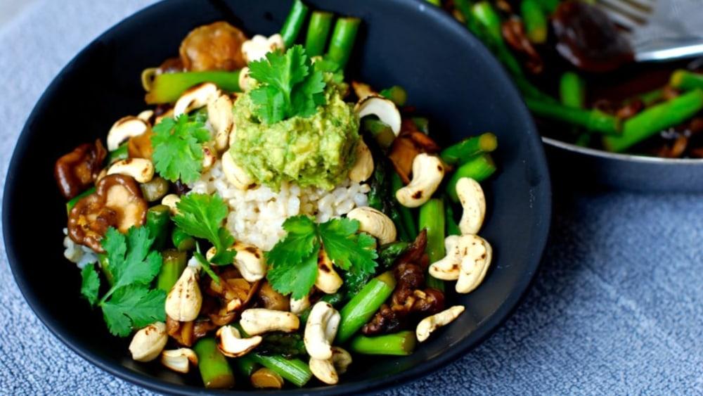 Image of Shiitake asparagus stir-fry with toasted cashews and wasabi avocado cream