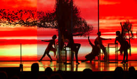 Dancers in front of orange background on stage