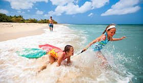 Carnival Cruise Lines girls swimming in Aruba with boogie boards