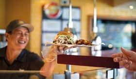Waiter handing juicy burger to patron