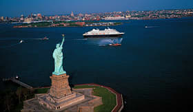 Holland America Line ship cruising past Statue of Liberty