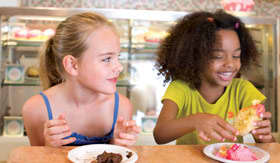 Two young girls, around age 5, eating cupcakes