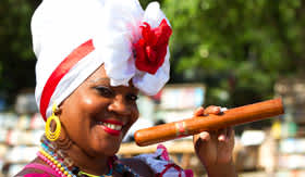 Woman Dressed in Colorful Headdress with Cuban Cigar - Regent Seven Seas Cruises