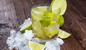 Regent Seven Seas Cruises glass of caipirinha with crushed ice on wooden background