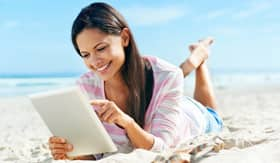 Woman using a tablet on the beach