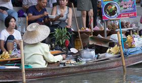 A vendor sells her wares in an on-water marketplace in Bangkok