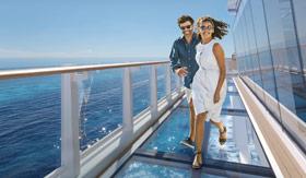 A couple enjoying the glass-bottom Oceanwalk on Ocean Boulevard on Norwegian Prima