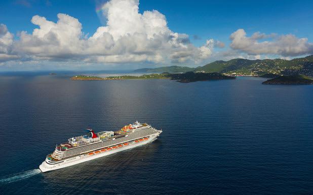 Long shot of Carnival Horizon sailing in deep blue water toward a green island
