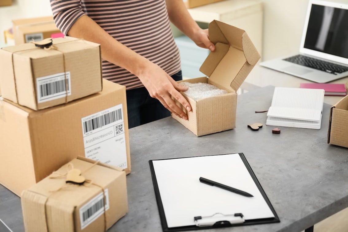 Verschicken von e-Commerce Sendungen dargestellt durch eine Hand, dass ein Paket packt