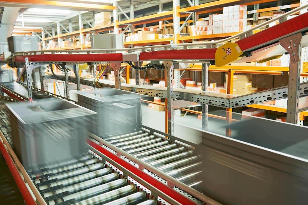 Paketbox in grau auf Paketband in Bewegung als Darstellung von Predictiv und vorhersagender Versand