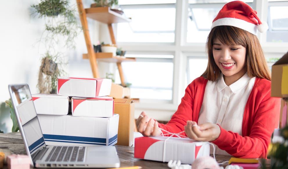 Frau in Weihnachtsmannkostüm beim Verpacken eines Paketes für Aktionslogistik und Salespromotion