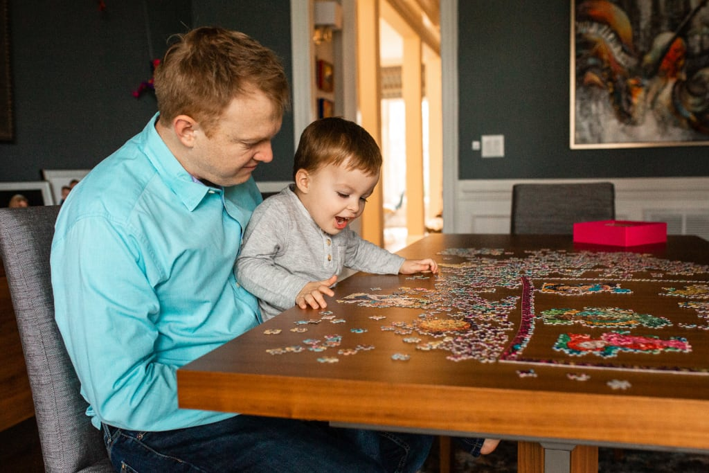 dad with boy playing puzzle lifestyle photo session raleigh
