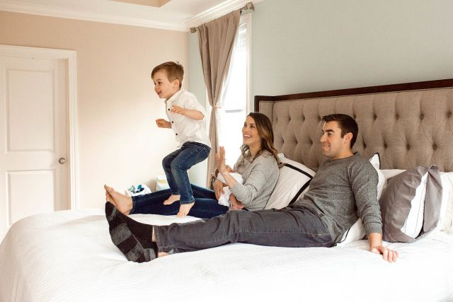 boy jumping on a bed lifestyle family photoshoot with newborn