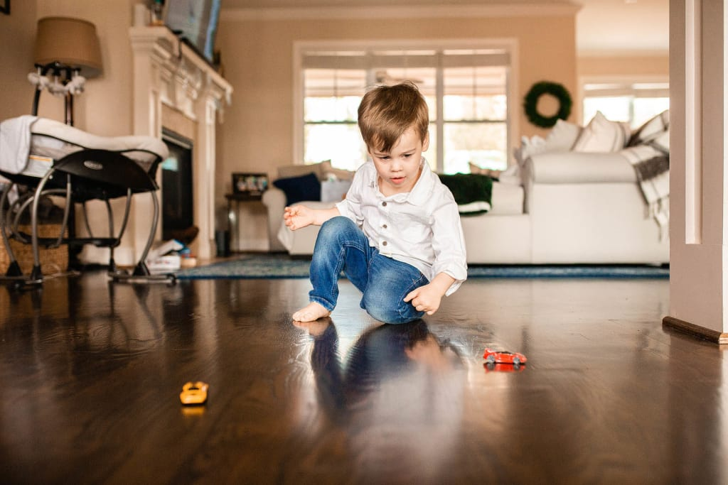candid family portrait boy is playing with hot wheels lifestyle in-home photo session raleigh nc