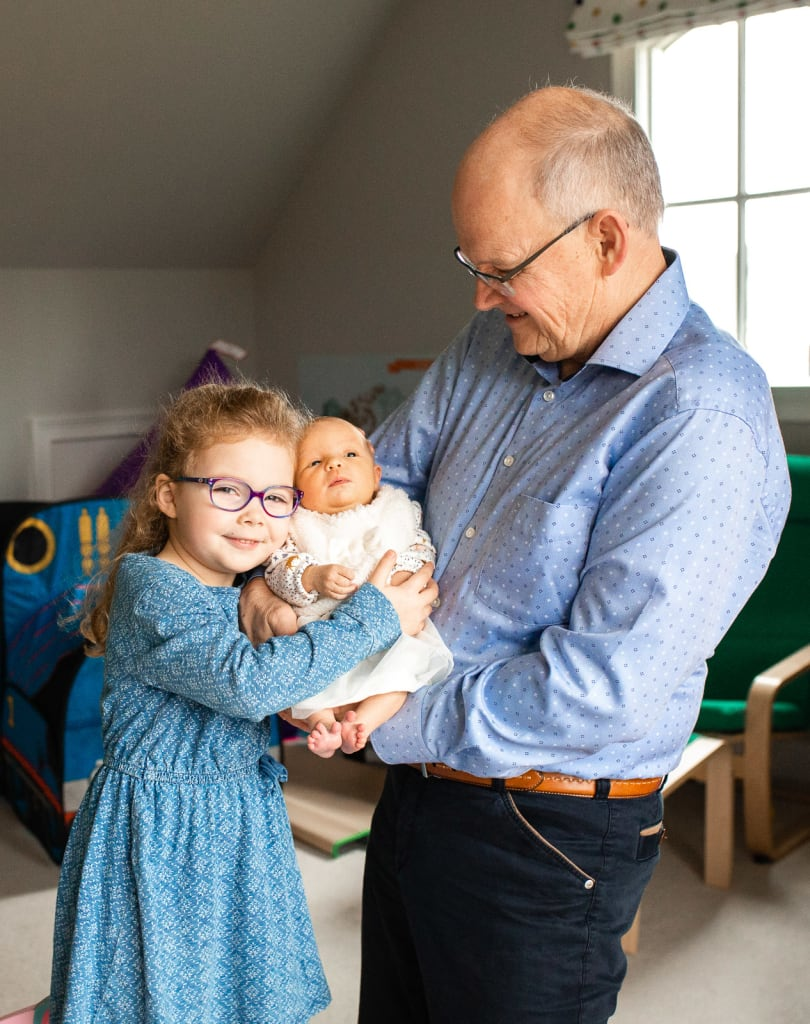 grandfather with 2 baby girls in-home photo session with lifestyle family photographer raleigh nc
