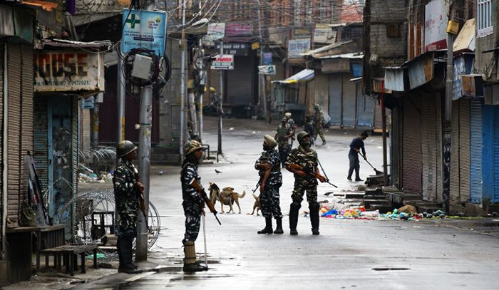 Paramilitary soldiers stand guard on a deserted street during curfew in Srinagar-kashmir-Article 370