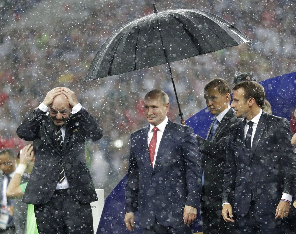 FIFA President Gianni Infantino, left, gestures as Russian President Vladimir Putin stands underneath an umbrella watched by French President Emmanuel Macron after the final match between France and Croatia