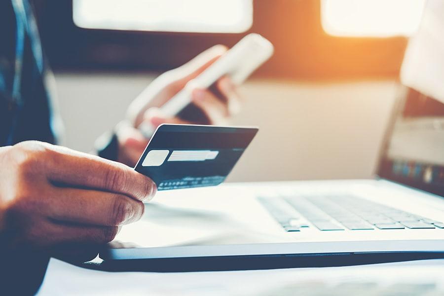 Homme qui tient une carte bancaire dans sa main pour effectuer un achat en ligne