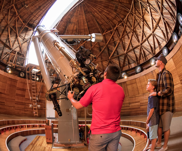 Two men and a boy look through a giant telescope at the sky