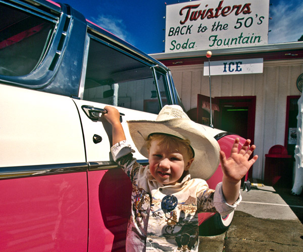 A little boy in a cowboy costume stands next to a pink and white vintage car in front of Twisters restaurant