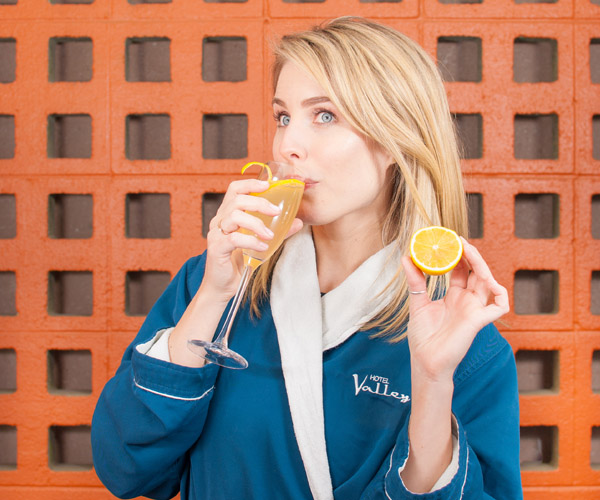 A blonde girl in a blue bathrobe drinks an orange cocktail