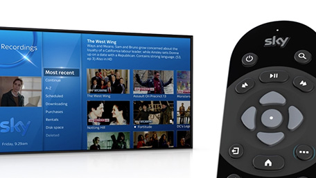 Image of Sky Q remote with Sky Q Home screen showing in background