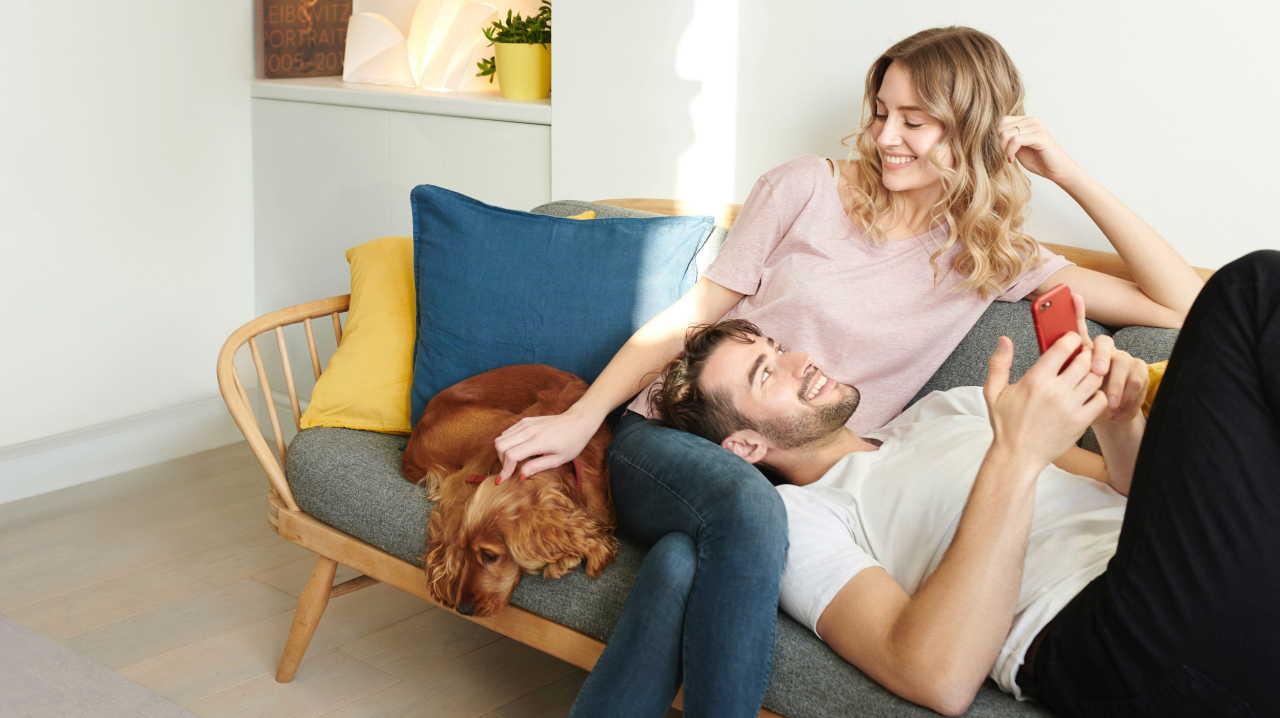 Couple de détente sur leur canapé avec un chien dans un appartement moderne