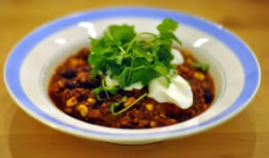 Plat de chili avec coriandre et crême fraîche.