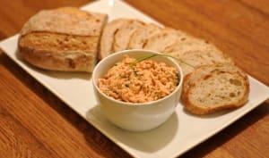 Rillettes de saumon dans un bol avec quelques tranches de pain frais