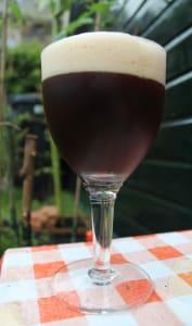 Verre de bière brune avec mousse