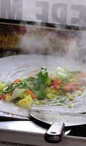 Cuisson d'un dosa garni de salade et légumes divers